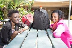 Młodzi Czarni ucznie siedzi przy bakłaszką Zdjęcie Royalty Free