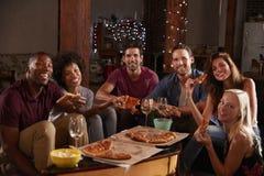 Młodzi dorosli je pizzę przy partyjnym spojrzeniem kamera fotografia stock