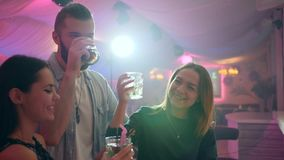 Młodzi dorosli robią grzance i piją koktajle przy wieczór przyjęciem przeciw tłu jaskrawi świetlicowi światła zbiory wideo