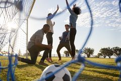 Młodzi dorosli rozwesela zdobywającego punkty cel przy meczem futbolowym zdjęcie royalty free