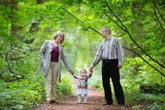 Młodzi dziadkowie chodzi z ich dziecko wnuczką Zdjęcia Stock