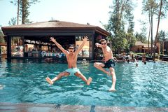 Młodzi faceci i dziewczyny skaczą w basen obraz royalty free