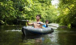 Młodzi faceci w łodzi z wiosłami na rzece przeciw tłu zieleni drzewa nad wodą Kayakers w kajaku obrazy royalty free