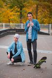 Młodzi faceta i dziewczyny deskorolkarze na jaskrawym jesień dniu, outdoors Obraz Stock