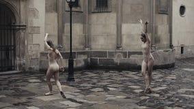 Młodzi fachowi żeńscy tancerze wykonują akrobatycznego tana wzdłuż średniowiecznej ulicy pod deszczem dziewczyny mokre zbiory wideo
