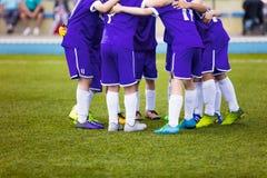 Młodzi futbolowi gracze piłki nożnej w zmroku - błękitny sportswear Młoda sport drużyna Zdjęcie Stock