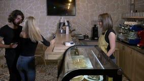 Młodzi i piękni klienci w sklep z kawą rozkazuje napojach i płacić z cryptocurrency bitcoin używać ich smartphone - zbiory wideo