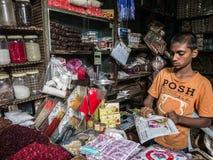 Młodzi Indiańscy sprzedawców stojaki za kolorowymi stosami bindi proszek w Devaraja wprowadzać na rynek Zdjęcie Royalty Free