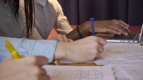 Młodzi kierownicy piszą obsiadaniu przy stołem z laptopem w wielkiej firmie zbiory