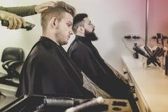 Młodzi klienci ma ich włosy ciącego fryzjerami obraz royalty free