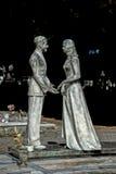 Młodzi kochankowie podczas gdy uśmiechnięta marmurowa statua Zdjęcia Royalty Free