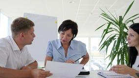 Młodzi kolaboranci z kobieta dyrektorem dyskutuje pomysłu rozwój biznesu na spotkaniu w nowożytnej sala posiedzeń