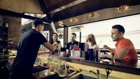Młodzi kumpel komunikują z each inny w barze firma a, spojrzenia jak barman robią alkoholiczce długim koktajlom zbiory