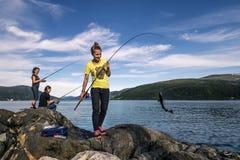 Młodzi ludzie łowią na skałach obok fjord, Norwegia Obraz Royalty Free