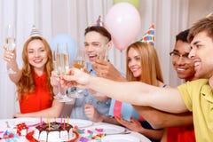 Młodzi ludzie świętuje urodzinowego obsiadanie przy zdjęcie stock