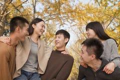 Młodzi ludzie bawić się piggyback w parku Fotografia Stock