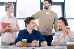 Młodzi ludzie biznesu patrzeje each inny przy miejscem pracy w małego biznesu biurze Fotografia Royalty Free