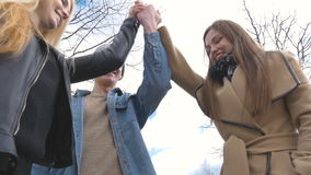 Młodzi ludzie chodzą w parku, mówją wiadomość, komunikują, śmiają się, dobry humor Stawia twój ręki wpólnie zbiory