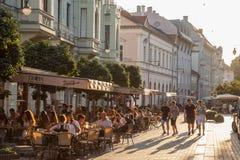 Młodzi ludzie chodzi na zwyczajnej ulicie Szeged, Południowy Węgry z innymi ludźmi siedzi na stołach w kawiarniach & restauraci, fotografia stock