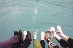 Młodzi ludzie chwyt nóg nad wodą Zdjęcia Royalty Free