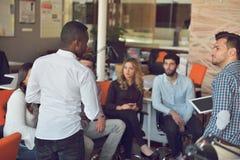 Młodzi ludzie grupują w nowożytnym biurze drużynowego spotkania i brainstorming podczas gdy pracujący na laptopie i pijący kawę obrazy stock