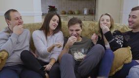 Młodzi ludzie jedzą popkorn i oglądają film w domu zbiory wideo