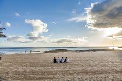 Młodzi ludzie jest ubranym Bro zbiorniki siedzą przy plażą Zdjęcia Stock