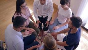 Młodzi ludzie na grupowej terapii sesi siedzi w okręgu biorą each inny ręki zbiory wideo