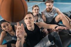 Młodzi ludzie patrzeje mężczyzna równoważenia piłkę na palcu Obraz Royalty Free