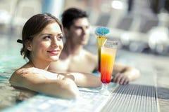 Młodzi ludzie pije koktajle pływackim basenem relaxin i Obrazy Royalty Free