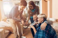 Młodzi ludzie przychodzili odwiedzać starego mężczyzna kobiety w karmiącym domu i Zdjęcia Stock