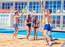 Młodzi ludzie przyglądającego szczęśliwego tana przy pływackim basenem Zdjęcia Royalty Free