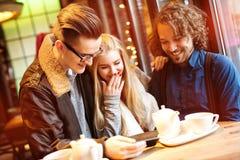 Młodzi ludzie - przyjaciele ma zabawę, patrzeje telefon Obraz Royalty Free