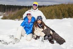 Młodzi ludzie siedzi na ono uśmiecha się i śniegu obrazy royalty free
