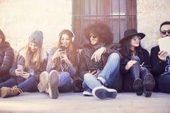 Młodzi ludzie siedzi na podłoga cieszy się ich czas wolnego obraz stock