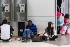 Młodzi ludzie siedzi na podłoga i czeka ich lot przy Doha lotniskiem międzynarodowym Fotografia Royalty Free