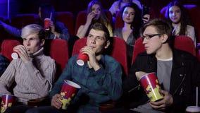 Młodzi ludzie siedzi przy kinem, ogląda film i je wystrzał kukurudzy, zbiory
