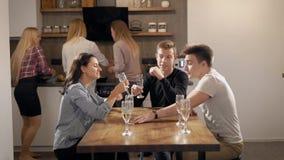 Młodzi ludzie siedzi przy stołem z jedzeniem i napojami zdjęcie wideo