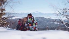 Młodzi ludzie w eleganckiej zimy odzieży Przystojna młoda chłopiec całuje jego uroczej dziewczyny w czole podczas gdy siedzący na zbiory