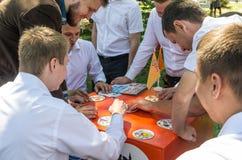Młodzi ludzie w parkowej sztuce Dobble gra planszowa zdjęcia royalty free
