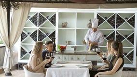 Młodzi ludzie w restauracyjnym pije winie w tle kucharz przygotowywa zbiory