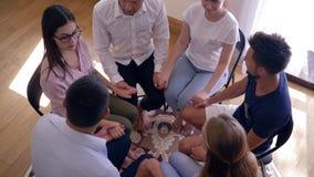Młodzi ludzie wspierają each mienia inne ręki podczas grupowego terapii sesi obsiadania w okręgu na krzesłach zbiory