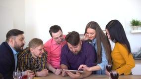 Młodzi ludzie z technologią przyjaciele używa cyfrowego pastylka komputer indoors i one oglądają foto Przyjaciół wieszać zbiory wideo