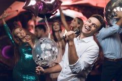Młodzi ludzie zabawę w klubie nocnym i śpiewają w karaoke W przedpolu jest mężczyzna w białej koszula Zdjęcie Stock