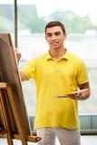 Młodzi męscy artysty rysunku obrazki w jaskrawym studiu Fotografia Stock