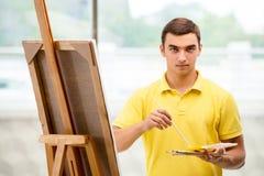 Młodzi męscy artysty rysunku obrazki w jaskrawym studiu Zdjęcia Stock
