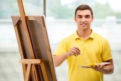Młodzi męscy artysty rysunku obrazki w jaskrawym studiu Obraz Stock