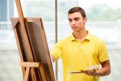 Młodzi męscy artysty rysunku obrazki w jaskrawym studiu Zdjęcie Stock