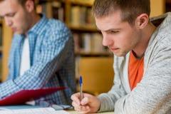 Młodzi męscy ucznie pisze notatkach przy bibliotecznym biurkiem Zdjęcie Royalty Free