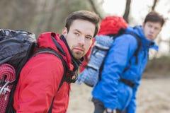 Młodzi męscy wycieczkowicze patrzeje daleko od w lesie Obraz Stock